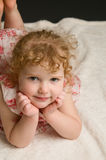 Addorable little curly haired girl. Four year old curly haired girl laying on the floor looking up at the camera and smiling Stock Photography