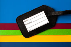 Address label of black leather. With room for name, address and telephone number situated on a colorful paper background Stock Image