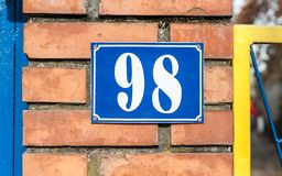 Old vintage house address blue metal number 98 on the gate and mail or letter box of residential building exterior wall on royalty free stock images