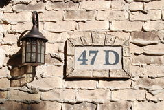 Address on Weeping Mortar Brick Wall. A glass lamp and an address sign are affixed to a brick wall. The bricks were laid using weeping mortar joints Royalty Free Stock Photo