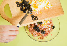 Adds grated eggs and  sliced olives in mincemeat. 