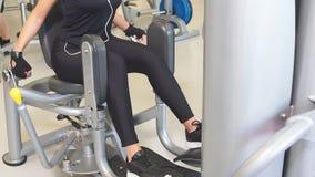 Adduction lub porywacz maszyna dysponowana dziewczyna ćwiczy ona nogi w gym zdjęcie wideo
