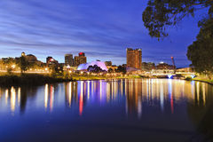 ADE CBD River sunrise. Panoramic view of Adelaide's CBD reflecting in still torrens river waters with bright lights and illumination royalty free stock photography