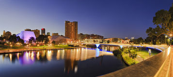 ADE river Rise 2 panorama. Brightly lit Adelaide city CBD with foot bridge across Torrens river. Illumination reflecting in calm waters at sunrise royalty free stock photo