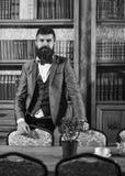 Adel, Luxuslebensstil, Erfolg, Eleganzkonzept Reicher mit ruhigem Gesicht nahe Bücherschrank Lizenzfreie Stockfotos