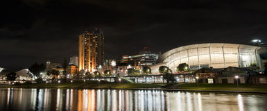 Adelaide by Night. Adelaide skyline illuminated at night, lights reflecting in the torrens lake stock image