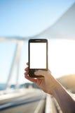 Adelgace la mano femenina que sostiene un teléfono y fotografió la visión desde el puente Imagen de archivo
