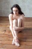 Adelgace a la muchacha desnuda hermosa que se sienta en las piernas del piso cruzadas Imagen de archivo