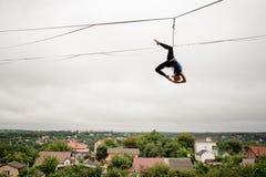 Adelgace a la muchacha rubia que equilibra arriba en un slackline contra el cielo y la ciudad grises foto de archivo libre de regalías