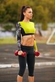Adelgace a la mujer atlética con pesas de gimnasia en el estadio Muchacha atractiva deportiva con entrenamiento plano del vientre imágenes de archivo libres de regalías
