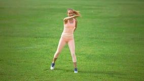Adelgace a la mujer atlética que hace ejercicios en hierba verde almacen de video