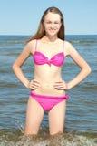 Adelgace a la mujer hermosa que se coloca en el mar en la playa Foto de archivo libre de regalías