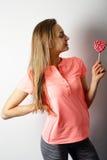 Adelgace a la mujer hermosa que sostiene y que mira la piruleta en el sh Foto de archivo libre de regalías