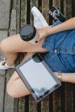 Adelgace a la mujer joven que se sienta en banco con la taza de café Foto de archivo