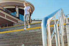 Adelgace a la mujer mayor en el equipo deportivo que corre abajo de las escaleras Fotografía de archivo libre de regalías
