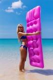 Adelgace a la mujer rubia con la playa del trópico del colchón de aire imagen de archivo libre de regalías