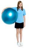 Adelgace y ajuste a la muchacha adolescente que sostiene una bola suiza Imagen de archivo libre de regalías