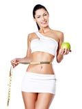 Adelgazar a la mujer con una cinta métrica y una manzana Imagen de archivo libre de regalías