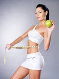 Adelgazar a la mujer con una cinta y una manzana de medición Fotografía de archivo