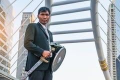 Adeln Sie den Geschäftsmann, der eine Helm- und Stahlklinge trägt Stockfotografie