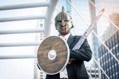 Adeln Sie den Geschäftsmann, der eine Helm- und Stahlklinge trägt In der Stadt Lizenzfreies Stockfoto