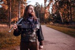 Adeln Sie im Waldkerl im mittelalterlichen Kostüm mit Klinge Stockfotografie