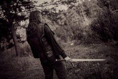 Adeln Sie im Waldkerl im mittelalterlichen Kostüm mit Klinge Lizenzfreie Stockfotos