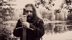 Adeln Sie im Waldkerl im mittelalterlichen Kostüm mit Klinge Lizenzfreie Stockfotografie