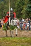Adeln Sie Sturzhelm und Schild zu Pferd durch das Turnier Stockfoto