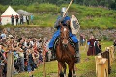 Adeln Sie Sturzhelm und Schild zu Pferd durch das Turnier Stockbild
