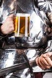 adeln Sie tragende Rüstung und Haltenbecher Bier und beidhändiges swor Lizenzfreie Stockfotos
