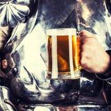 adeln Sie tragende Rüstung und Haltenbecher Bier und beidhändiges swor Stockfoto