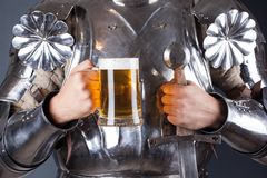adeln Sie tragende Rüstung und Haltenbecher Bier und beidhändiges swor Stockfotos