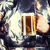 adeln Sie tragende Rüstung und Haltenbecher Bier und beidhändiges swor Lizenzfreies Stockfoto