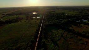 Adembenemende antenne van een goederentrein die door platteland overgaat stock videobeelden