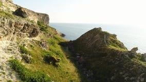 Adembenemende die helling met rotsen en groen gras boven het blauwe overzees en de heldere hemel, de zomeraard wordt behandeld sc stock video