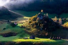 Adembenemende mening over ver die dorp in mist bij gouden uur, Fundatura Ponorului, Hunedoara-provincie, Roemeni? wordt behandeld stock fotografie