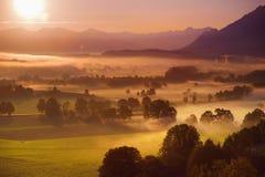 Adembenemende ochtend lansdcape van klein Beiers die dorp in mist wordt behandeld Toneelmening van Beierse Alpen bij zonsopgang m stock fotografie