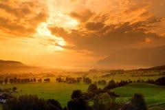Adembenemende ochtend lansdcape van klein Beiers die dorp in mist wordt behandeld Toneelmening van Beierse Alpen bij zonsopgang m royalty-vrije stock fotografie