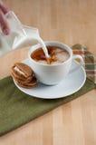 Adentro taza vertida leche de té negro Imagen de archivo