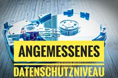 Adequate Data Protection Level. An opened hard drive with the German text 'Angemessenes Datenschutzniveau' for adequate data protection level Stock Photography