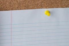 Aderência de polegar amarela que guarda de papel em Cork Board Fotografia de Stock