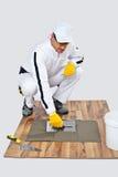 Adesivo da telha dos applyes do trabalhador da construção no assoalho de madeira Imagens de Stock Royalty Free
