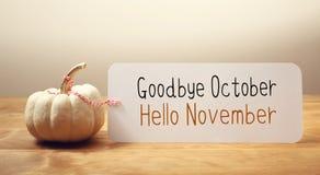 Adeus mensagem de outubro olá! novembro com uma abóbora pequena fotos de stock royalty free