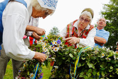 Adhère la guirlande des fleurs au mât Photo stock
