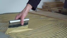 Adhésif appliqué de travailleur pour le parquet Autoguidez la rénovation clips vidéos