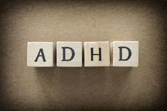ADHD abbreviation on wooden blocks. ADHD is Attention deficit hyperactivity disorder. Close up. Vignette Royalty Free Stock Images