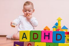 ADHD-Concept De baby speelt met kleurrijke kubussen met brieven Stock Foto's
