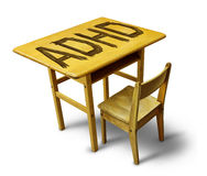 ADHD Concept. For hyperactivity disorder and attention deficit  behavior as a school desk with the letters carved into the wooden table as a healthcare symbol Stock Image