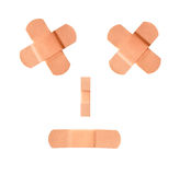 Adhesive bandages making a sad frown face. Two adhesive first-aid bandages are crossed over one another to form and X for the eyes. The mouth frowns Stock Photo